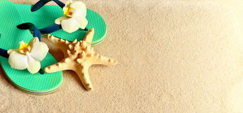 Flip Flops in the sand with starfish . Summertime .beach concept. Stock Photos