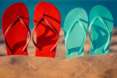 Flip-flops on the sand. Two pair flip-flops on the sand. Summer vacation concept stock photography