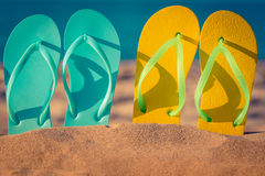 Flip-flops on the sand. Two pair flip-flops on the sand. Summer vacation concept royalty free stock images