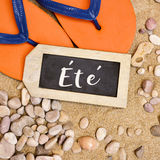 Flip-flops on the sand and word ete, summer in french Royalty Free Stock Image
