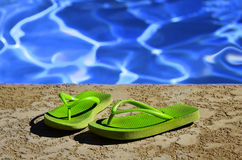 Flip Flops Sandals by Swimming Pool. Detail of flip flops sandals by swimming pool Royalty Free Stock Image