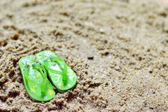 Flip flops on the sandy beach. Green flip flops on the sandy beach royalty free stock photos