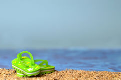 Flip flops on the sandy beach. Green flip flops on the sandy beach with sea water and sky in background stock photos