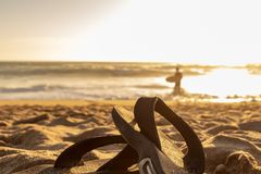 Flip Flops on a sandy beach at sunset royalty free stock photography