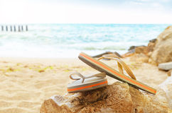 Flip flops on a sandy ocean beach. On background of ocean Stock Images
