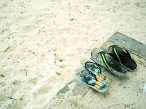 Flip flops on a sandy ocean beach stock photography