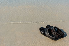 Flip flops on a sandy ocean beach Stock Photo