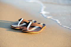 Flip flops on a sandy ocean beach Royalty Free Stock Images