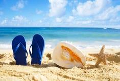 Flip flops, seashell and starfish on sandy beach. Blue Flip flops, big seashell and starfish on sandy beach in Hawaii, Kauai Royalty Free Stock Photography