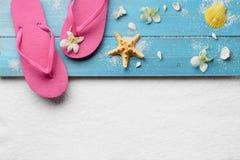 Flip-flops with seashells on beach. Flip-flops with seashells on sand beach royalty free stock image