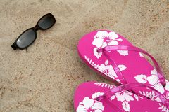 Flip-flops and shades. Sun glasses and pink flip-flops in the sand at the beach royalty free stock photos