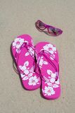 Flip-flops and shades. Pink flip-flops and sun glasses on the sand at the beach royalty free stock photo