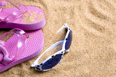 Flip flops and shades on beach Stock Photo