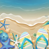 Flip-flops and shells on the beach. royalty free stock photography