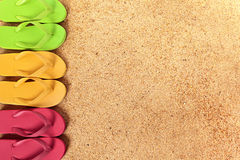 Flip flops side edge row, beach sand background, copy space Stock Photos