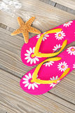 Flip flops and starfish on dock. Pretty flip flop sandals on beach dock by starfish Stock Photography