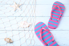 Flip flops with starfish. Pair of flip flops with fishnet and starfish on wooden table stock photos