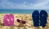 Flip flops and starfish with sunglasses on sandy beach. With adult and child in the ocean on background Stock Image