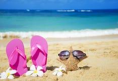 Flip flops and starfish with sunglasses on sandy beach. Flip flops and starfish with sunglasses with tropical flowers on sandy beach in Hawaii, Kauai Stock Image
