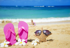 Flip flops and starfish with sunglasses on sandy beach. Flip flops and starfish with sunglasses with tropical flowers on sandy beach with playing girl by the sea Stock Photography