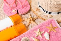 Flip flops, straw hat, starfish, sunscreen bottle, body lotion spray on wooden background top view . flat lay summer beach sea. Accessories background, holiday stock photos