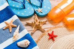Flip flops, straw hat, starfish, sunscreen bottle, body lotion spray on wooden background top view . flat lay summer beach sea. Accessories background, vacation stock photo