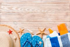 Flip flops, straw hat, starfish, sunscreen bottle, body lotion spray on wooden background top view . flat lay summer beach sea. Accessories background, vacation royalty free stock image