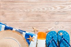 Flip flops, straw hat, starfish, sunscreen bottle, body lotion spray on wooden background top view . flat lay summer beach sea. Accessories background, travel stock photography