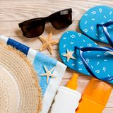 Flip flops, straw hat, starfish, sunscreen bottle, body lotion spray on wooden background top view . flat lay summer beach sea. Accessories background, holiday royalty free stock image