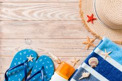 Flip flops, straw hat, starfish, sunscreen bottle, body lotion spray on wooden background top view . flat lay summer beach sea. Accessories background, vacation stock image