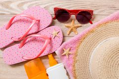 Flip flops, straw hat, starfish, sunscreen bottle, body lotion spray on wooden background top view . flat lay summer beach sea. Accessories background, travel royalty free stock image