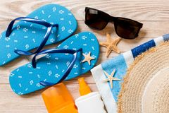 Flip flops, straw hat, starfish, sunscreen bottle, body lotion spray on wooden background top view . flat lay summer beach sea. Accessories background, holiday stock images