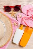 Flip flops, straw hat, starfish, sunscreen bottle, body lotion spray on wooden background top view . flat lay summer beach sea. Accessories background, vacation stock photos