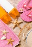 Flip flops, straw hat, starfish, sunscreen bottle, body lotion spray on wooden background top view . flat lay summer beach sea. Accessories background, travel stock image