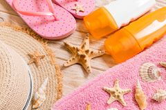 Flip flops, straw hat, starfish, sunscreen bottle, body lotion spray on wooden background top view . flat lay summer beach sea. Accessories background, vacation royalty free stock photography