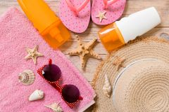 Flip flops, straw hat, starfish, sunscreen bottle, body lotion spray on wooden background top view . flat lay summer beach sea. Accessories background, vacation stock photography
