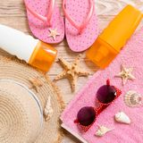 Flip flops, straw hat, starfish, sunscreen bottle, body lotion spray on wooden background top view . flat lay summer beach sea. Accessories background, holiday royalty free stock photo