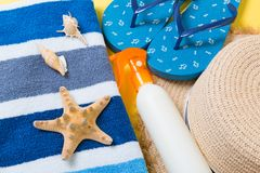 Flip flops, straw hat, starfish, sunscreen bottle, body lotion spray on yellow background top view . flat lay summer beach sea. Accessories background, holiday stock photos