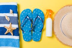 Flip flops, straw hat, starfish, sunscreen bottle, body lotion spray on yellow background top view . flat lay summer beach sea. Accessories background, travel royalty free stock images