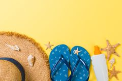 Flip flops, straw hat, starfish, sunscreen bottle, body lotion spray on yellow background top view . flat lay summer beach sea. Accessories background, vacation royalty free stock image