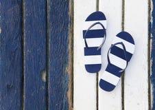 Flip Flops Striped. Striped flip-flops on color wooden background stock photo