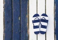 Flip Flops Striped. Striped flip-flops on color wooden background stock photos