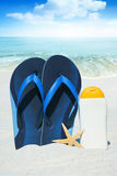 Flip Flops and Sun cream on the Beach Stock Photos