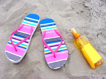 Flip-flops and suncare milk on a sandy beach. Summer time with flip-flops and suncare milk on a sandy beach Royalty Free Stock Photo