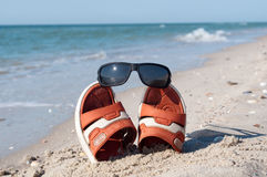 Flip-flops with sunglasses. In the sand Stock Photos