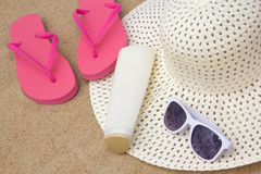 Flip flops, sunglasses, cream and hat on sandy beach Stock Photography