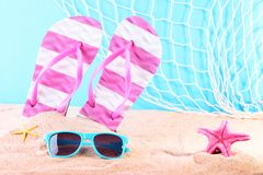 Flip flops with sunglasses. And starfish on the beach sand stock image