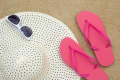 Flip flops, sunglasses and hat on sandy beach Stock Photos