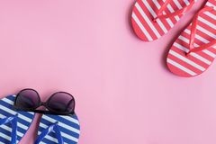 Flip flops and sunglasses on a pink background. Top view, flat lay stock photos