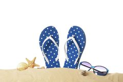 Flip-flops and sunglasses on sand against white background. Summer vacation concept Royalty Free Stock Photography